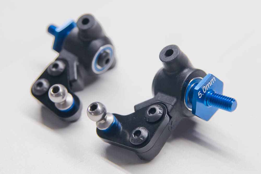 The steering blocks are next to be prepped and mounted in the front caster block. The bearings go in on either side (without a crush tube like the B5m did) followed by inserting the aluminum 5mm offset front axle. The metal steering blocks are attached to the steering block via two screws. The ball stud has a 2mm blue aluminum washer underneath and held in with a 3mm nut.