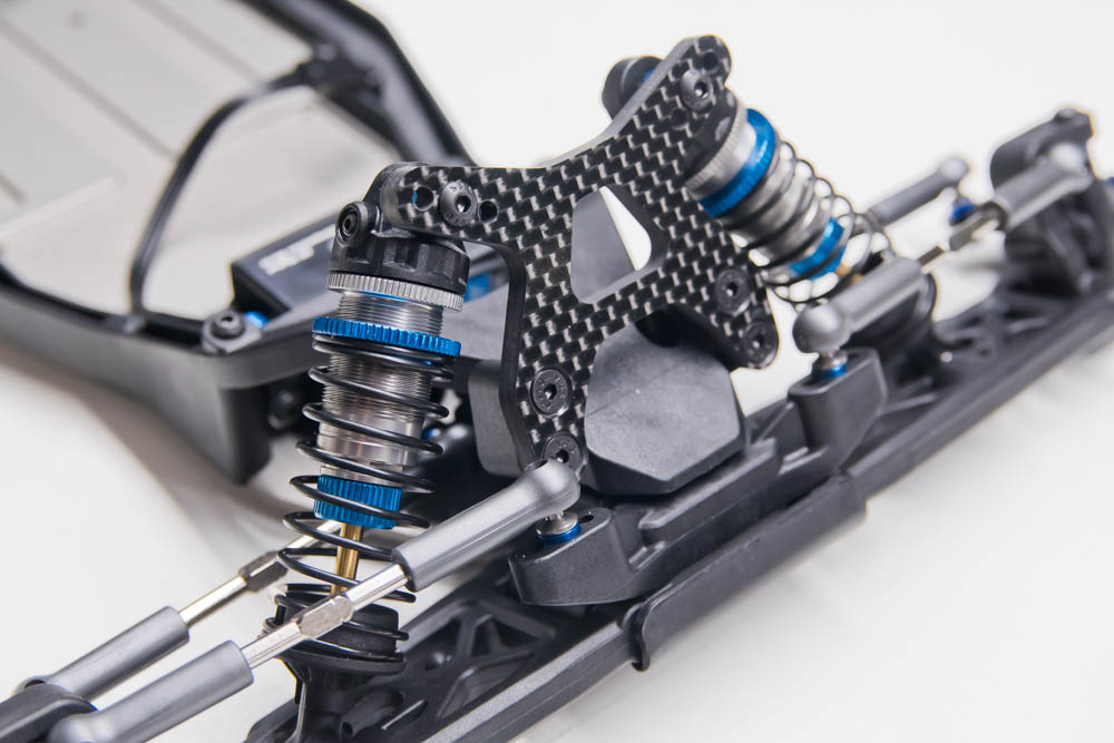 The front shocks mount to the suspension arm's outside hole using the LONG eyelet on the shock shaft.